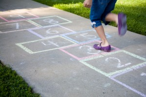 A young girl playing hopscotch on a sidewalk